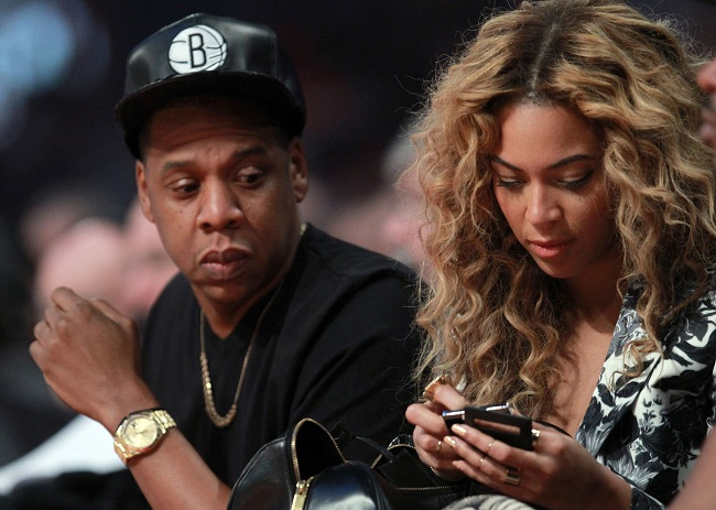HOUSTON, TX - FEBRUARY 17: Jay-Z looks over at wife Beyonce during the 2013 NBA All-Star game at the Toyota Center on February 17, 2013 in Houston, Texas. NOTE TO USER: User expressly acknowledges and agrees that, by downloading and or using this photograph, User is consenting to the terms and conditions of the Getty Images License Agreement. (Photo by Ronald Martinez/Getty Images)